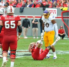 State's Ryan Finley was sacked just once on Saturday with Nate Harvey bringing him down in the second quarter. Shaun James (50) is beside the upended Wolfpack quarterback.