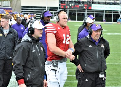 Holton Ahlers (12) is ready to signal a play call from offensive coordinator Donnie Kirkpatrick (black jacket, purple cap). (Photo by Al Myatt)