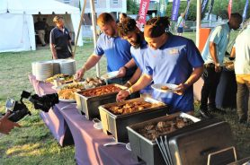 A trio of SMU Mustangs move down the serving line at the clambake. (Photo by Al Myatt)