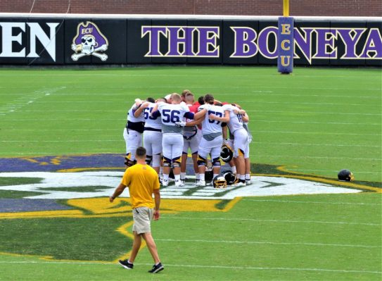 A group huddles at midfield after Saturday morning's scrimmage at Dowdy-Ficklen Stadium. (Photo by Al Myatt)