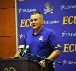 First-year East Carolina coach Mike Houston speaks to the media day gathering in Harvey Hall at the Murphy Center on Saturday. (Photo by Al Myatt)