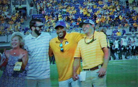 Harold Varner III (bright gold shirt), shown on the big screen, was welcomed back to his alma mater from the PGA Tour (Photo by Al Myatt)