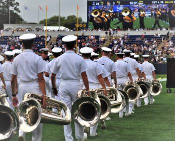Navy brass of the present, and possibly the future, walks the sideline before their halftime presentation