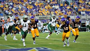 Pirates defenders Kendall Futrell (44), Gerard Stringer (30) and Bruce Bivens (38) move to contain William & Mary quarterback Hollis Mathis (Photo by Al Myatt)