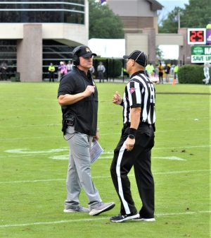 ECU coach Mike Houston talks to an official as an interception call is reviewed and subsequently overturned, keeping the ball in the Pirates' possession for a fourth-down punt. (Photo by Al Myatt)