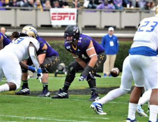 ECU senior center Branden Pena snaps the ball and looks to protect. (Photo by Al Myatt)