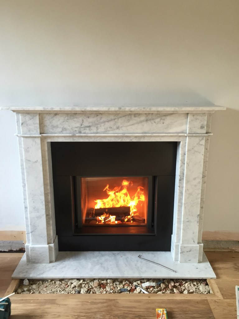Stuv 21/75 Single fronted wood burning stove with marble surround installation