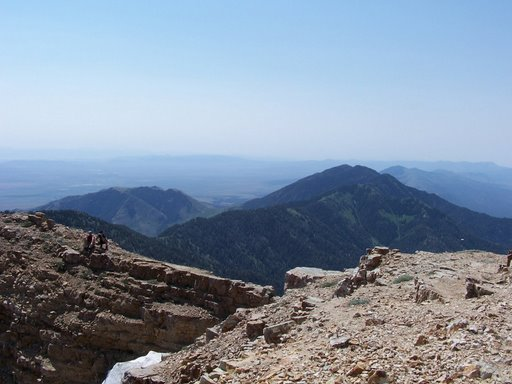 Two hikers sit on a cliff just south of Deseret Peak's summit (photo by Clint Thomsen)