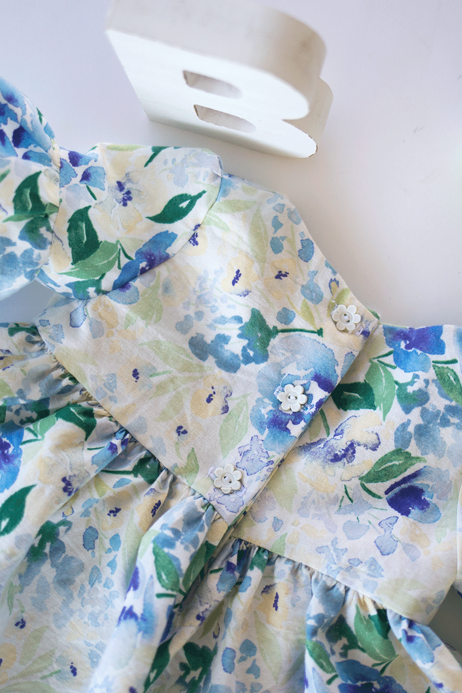 This simple pattern hack will show you how to make a darling on-trend bell sleeve baby dress DIY for the little bundle of joy! Take a break from pink by using this beautiful blue and green floral fabric; it's the perfect addition to any little girls' wardrobe. Read on for the ruffle sleeve tutorial and details on this gorgeous quilting cotton.