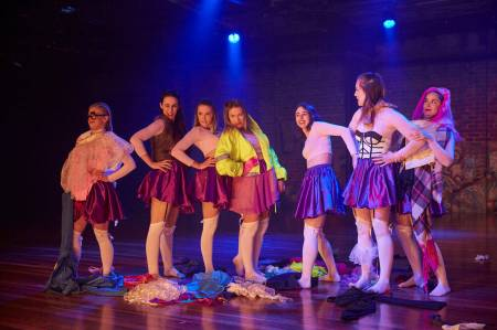 Seven females wearing pink fitted tops and shiny purple skirts. Some females have various other clothing items on including yellow high vis jacket, white and black corset and coke bottle glasses. They are standing in a straight line with their hand on their hip.