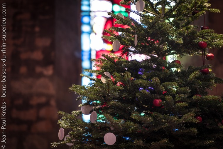 Sapin de Noël décoré de pommes rouges et d'hosties.