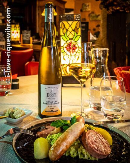"""A Riquewihr, il faut goûter à notre fameuse """"choucroute verte"""", la Riquewihrienne. C'est une étonnante choucroute crémeuse et douce préparée aux herbes fraîches et accompagnée de charcuterie poêlée (avec porc, oie et canard) inventée il y a 20 ans par François Kiener autrefois propriétaire du restaurant le Schoenenbourg (devenu aujourd'hui L'Originel) et étoilé Michelin en son temps. Un cahier des charges a été déposé pour la recette et les ingrédients. On ne trouve la Riquewihrienne qu'à Riquewihr. Un vrai délice, surtout pour ceux qui ne rafolent pas de l'acidité parfois exagérée de la choucroute traditionnelle."""