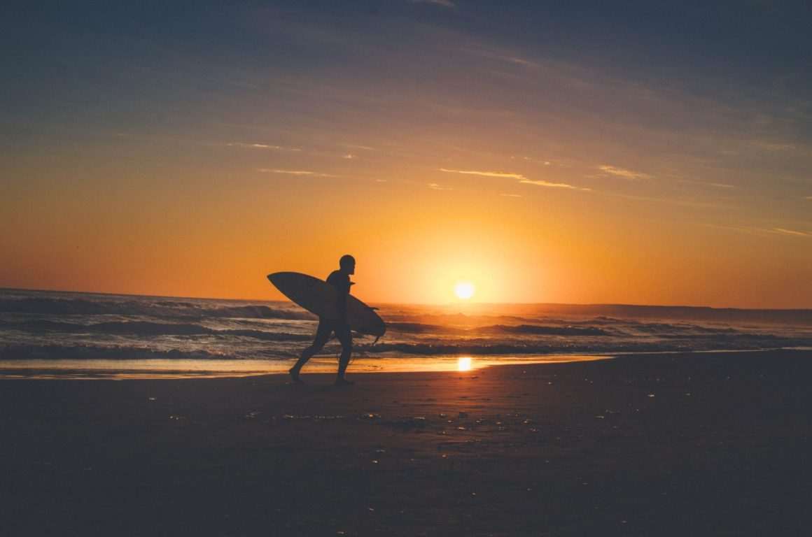 silhouette of person holding surfboard near body of water