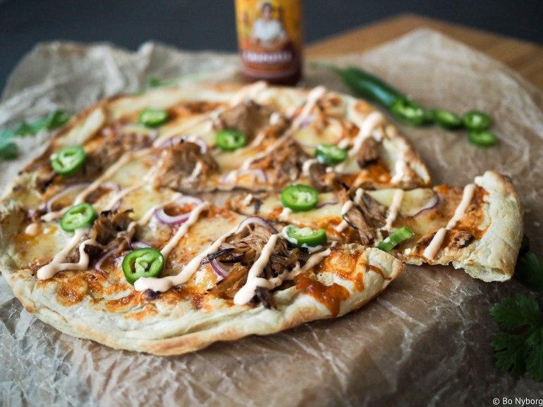 Jeg elsker pizza og det er kjempegøy å rigge til ordentlig pizzaverksted hjemme på kjøkkenet. Dessverre er det ikke hver dag man har tid, anledning og ork til å gå i gang med et sånt prosjekt og innimellom er det lov å jukse litt. De fleste grønnsaksforretninger selger libabrød, det er et mykt flattbrød som stammer fra vest-asia, dette brødet gjør en glimrende jobb som pizzabunn. Så er det bare å legge på den toppingen du har tilgjengelig. Jeg har brukt rester fra en pulled pork middag jeg nylig hadde.
