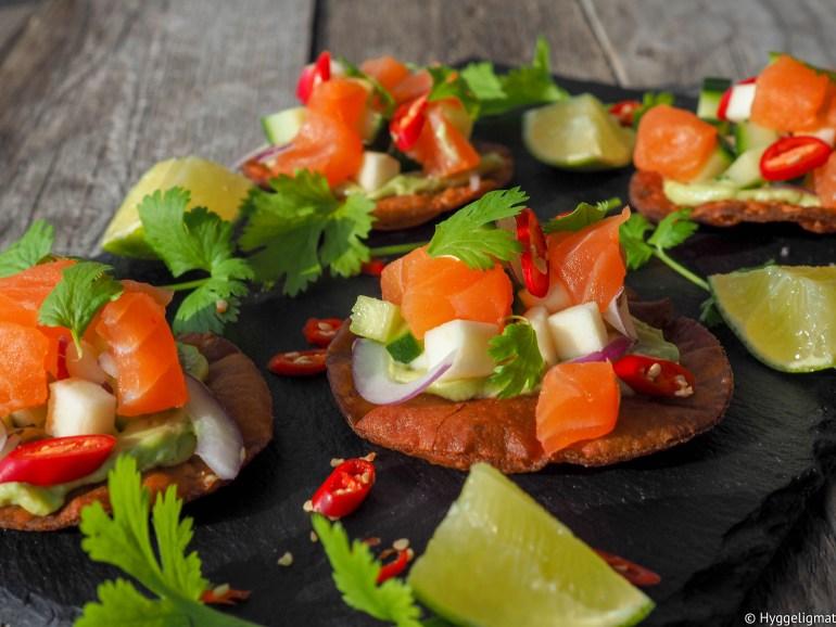 Tostadas er en mexicansk/latinamerikansk måte å servere en rett på. Ordet er spansk og betyr rett og slett ristet. Altså at retten inneholder en ristet eller fritert del, som er et av hovedelementene. Her har jeg fritert helt vanlige potetlomper slik at de blir en slags nacho. Disse har jeg toppet med en silkemyk avocadokrem, terninger av rå salmalaks og epler. Dette er skikkelig snadder.