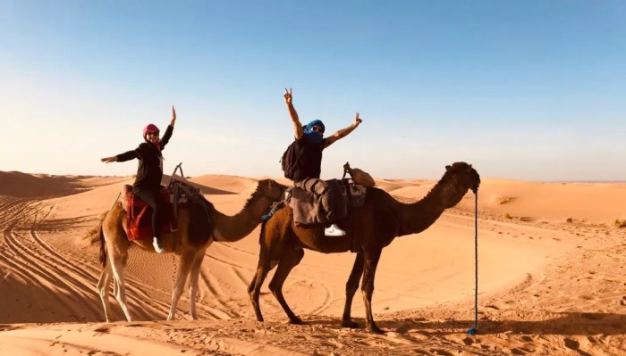 Two people ride camels in the Sahara Desert