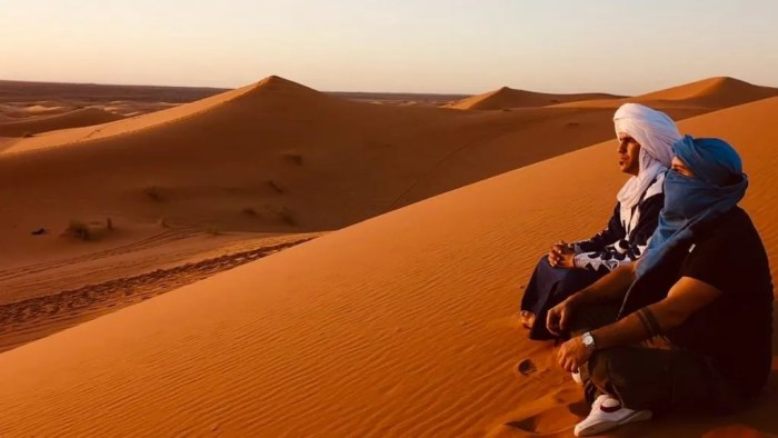 Two men sit in the Sahara Desert as the sun sets