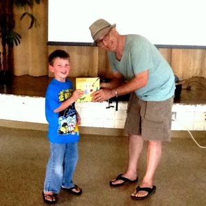 U.S. Author Barney Saltzberg gives a book to the Hanalei Elementary School library in Kauai.