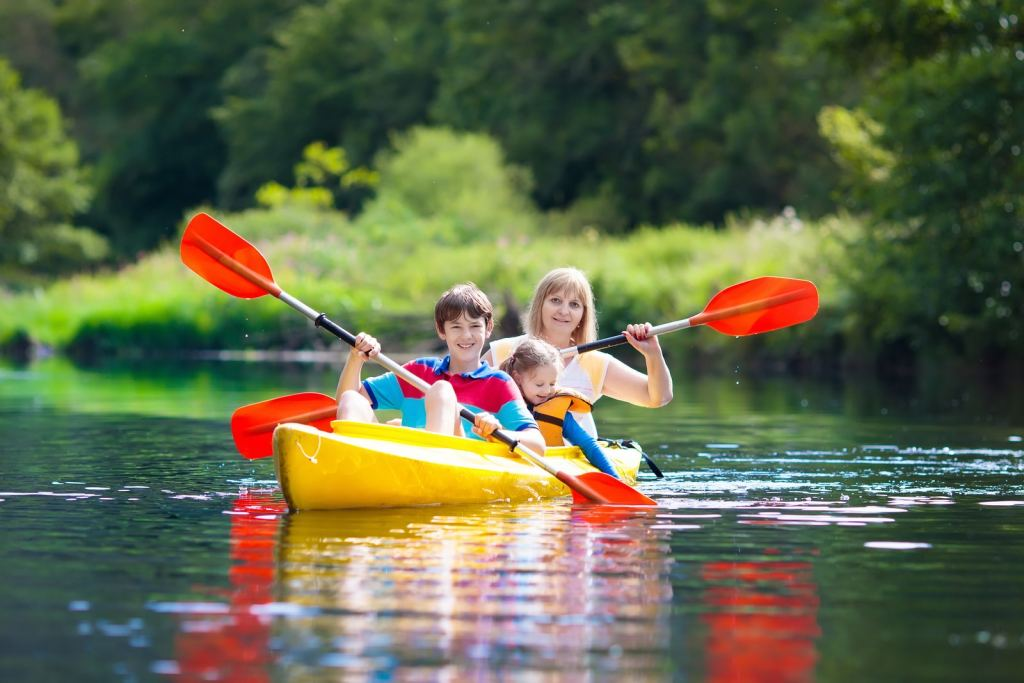 Child With Paddle On Kayak presented by Booking Express Travel