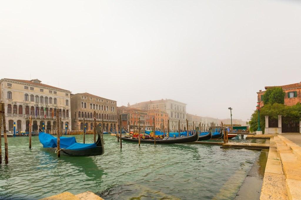 Gondolas moored in a foggy morning.
