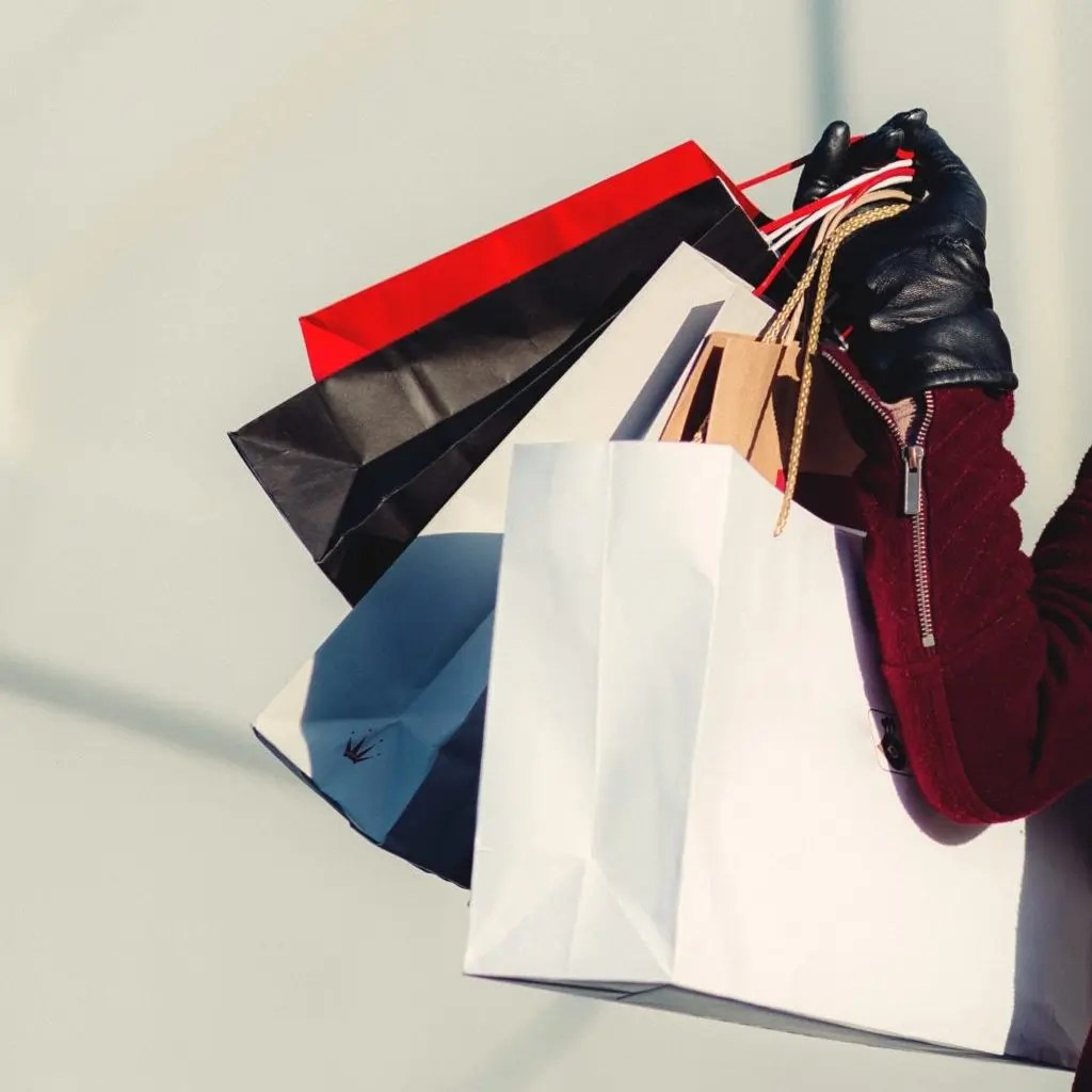 Close Up of paper shopping bags and women wearing red coat with black leather gloves