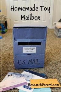 Homemade Toy Mailbox, with a blue outdoor mailbox, constructed homemade out of cardboard and supplies, for a child to play with indoors