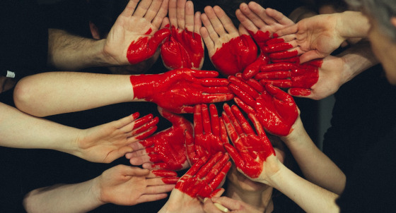 Hands with a large heart painted on them.