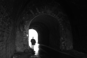 Figure Walking Toward Light through dark tunnel
