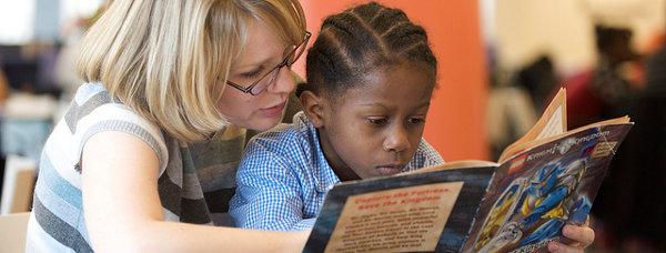 Teacher teaching child to read.
