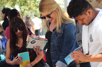 Fans get a hold of Advanced Readers Copies, some of the most coveted freebies at YALLWEST. (Saul Marquez, Bookstacked)