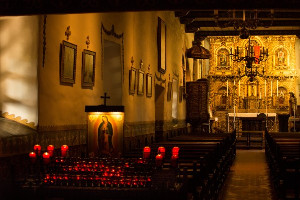 Candles burn in offering to the Virgin Mary in the chapel of Mission San Juan Capistrano.