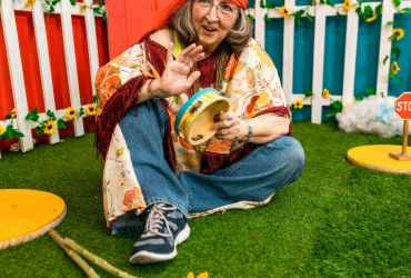 Woman In Blue Denim Jeans Sitting On Green Grass With A Tambourine