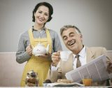 44583413 - 1950s beautiful woman serving tea for breakfast to her smiling husband