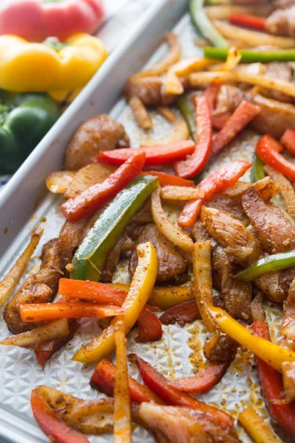 seasoned chicken fajitas and peppers on a sheet pan