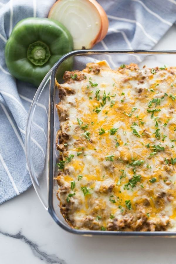 Mexican taco bake in a clear casserole dish with a green pepper and onion on the side