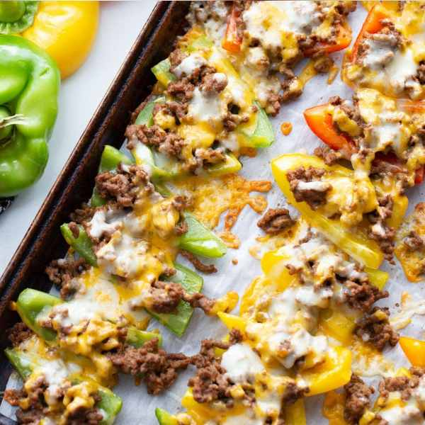 green, red and yellow bell peppers stuffed with ground beef and cheese on a baking sheet