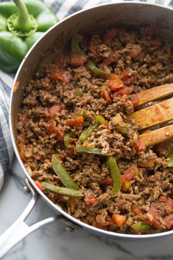taco seasoned ground beef with peppers in a skillet