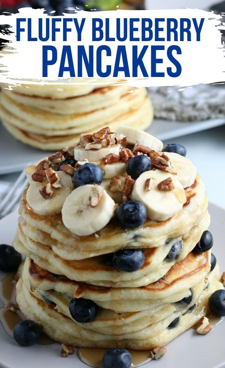 A stack of blueberry pancakes topped with bananas, bleuberries, and walnuts