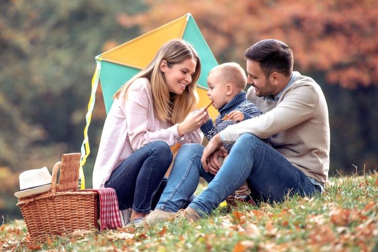 a young couple feeding their son on an autumn picnic