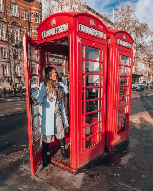 Lifestyle Instagram influencer @naohms, Naomi Genota, in a London telephone booth