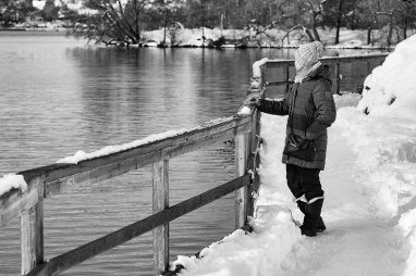 woman looking at river in snow