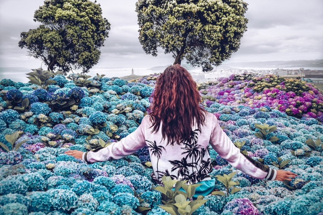 woman in forest of flowers toning her vagus