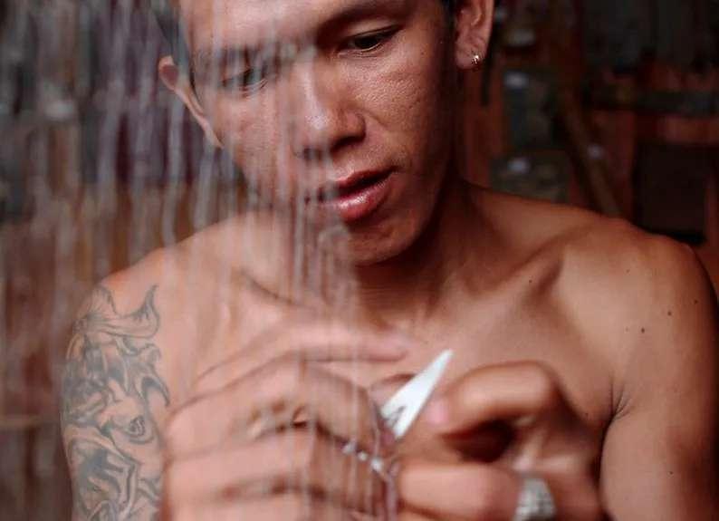 An Iban man repairs his fishing net at Nanga Sumpa, Ulu Ai, Sarawak, Malaysia.