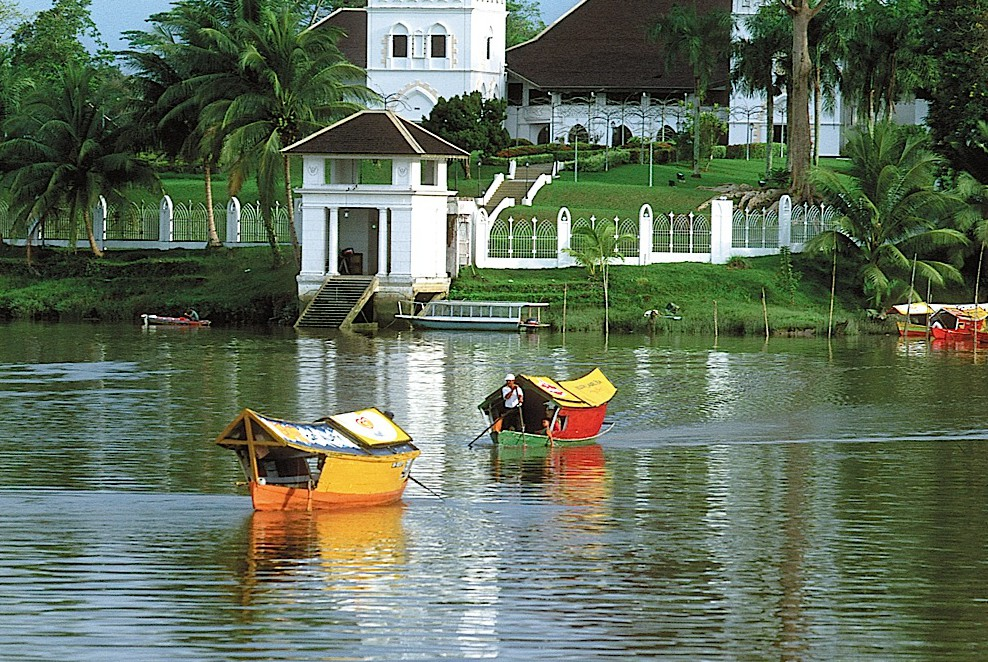 Sampans cross the Sarawak River in Kuching with the Astana in the background, Malaysia