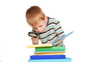 Dreng læser med lup