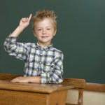 Skolebarn med hånden i vejret