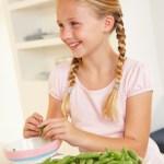 Pige bælger ærter og får nok frugt og grønt
