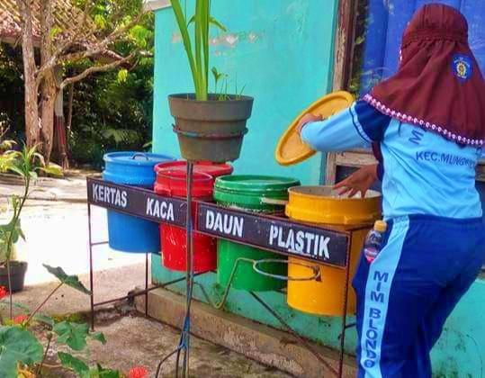 Salah satu siswa MI Muhammadiyah Blondo saat membuang sampah di sekitar rumahnya