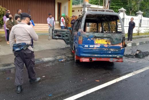 KORSLETING: Polisi mengamankan bangkai angkudes yang ludes terbakar. (Foto: ist)