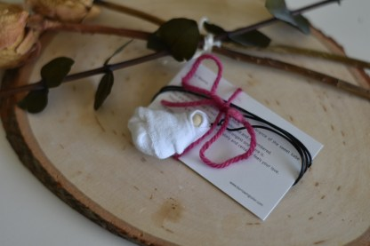 necklace with baby pendant on top of a notecard about infant loss and miscarriage